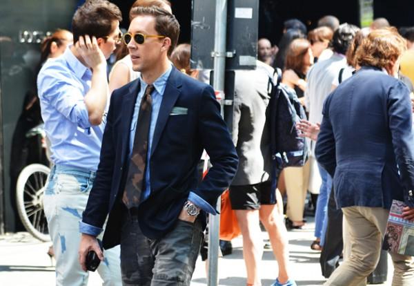 Мужчина в камуфляжных брюках, синем блейзере и галстуке камуфляжной расцветки