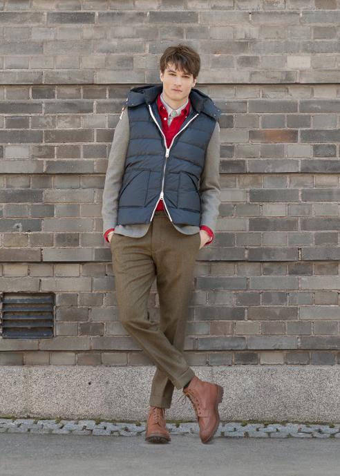Мужчина синем дутом жилете, зеленых шерстяных фланелевых брюках, Gant Rugger и высоких черных ботинках Tricker's