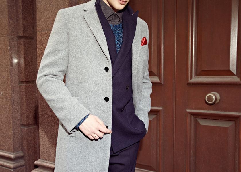 Мужчина в сером пальто, синем двубортном пиджаке, синем свитере, темной рубашке, все Reiss
