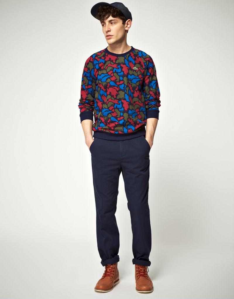 Мужчина в синих брюках-чинос, ботинках Red Wing, свитшоте с ярким камуфляжным принтом Lacoste Live!