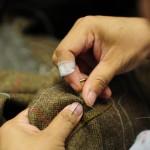 Обработка вручную отверстия под пуговицу на твидовом пиджаке