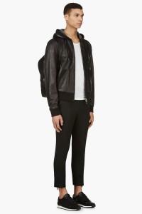 Мужчина в кожаной куртке с капюшоном Rag&Bone, чёрных кроссовках ETQ Amsterdam, укороченных узких брюках Undercover, c чёрным кожаным рюкзаком 3.1 Phillip Lim