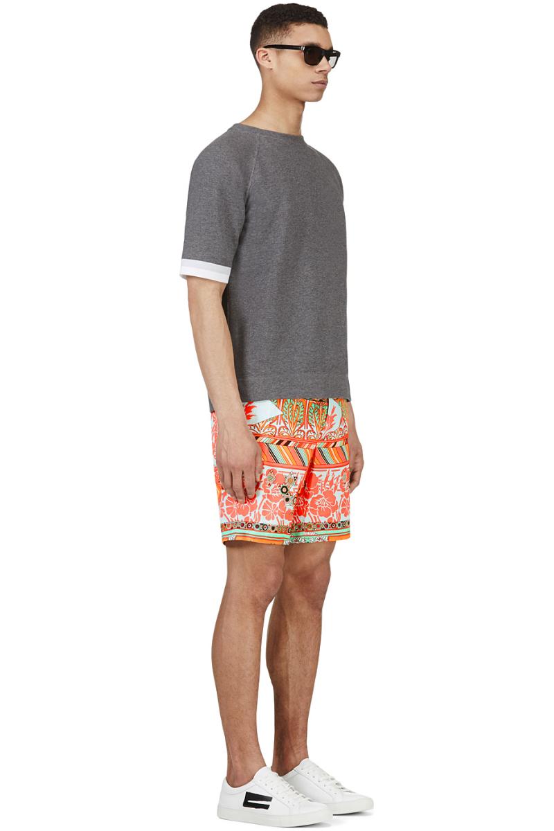 Мужчина в шортах-бермуда с ярким принтом кораллового цвета, MSGM