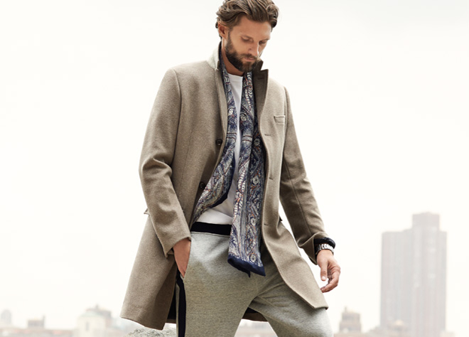 Мужчина в элегантном светлом пальто из шерсти и спортивных штанах