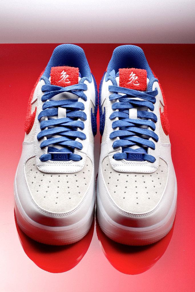 Пара белых кроссовок Nike AF1 с синими шнурками
