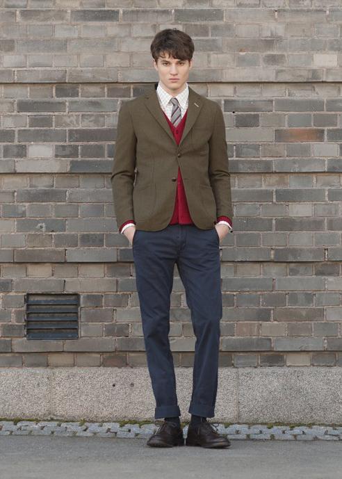 Мужчина в темно-зеленом спортивном пиджаке, красном кардигане и синих брюках-чинос, Gant Rugger и высоких ботинках Tricker's