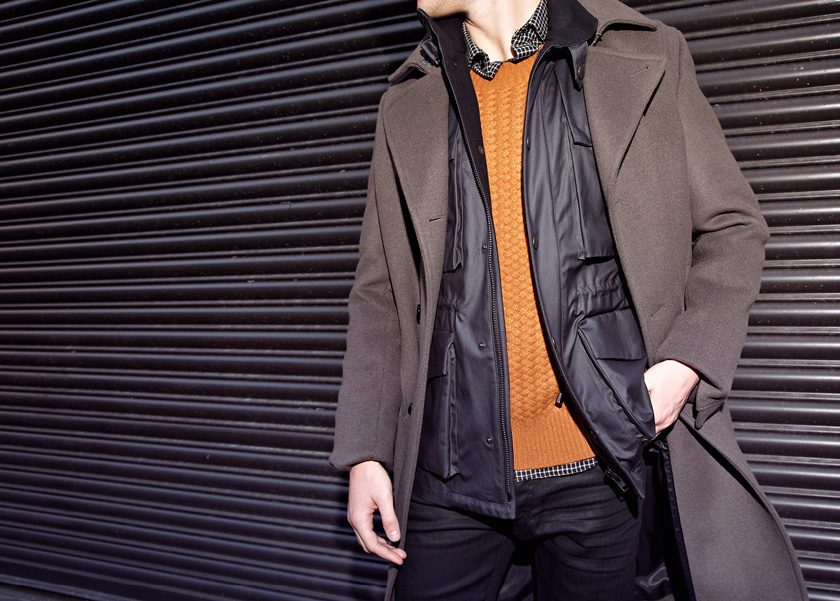 Мужчина в коричневом пальто, серой куртке, коричнево-желтом свитере, рубахе в клетку, все Reiss