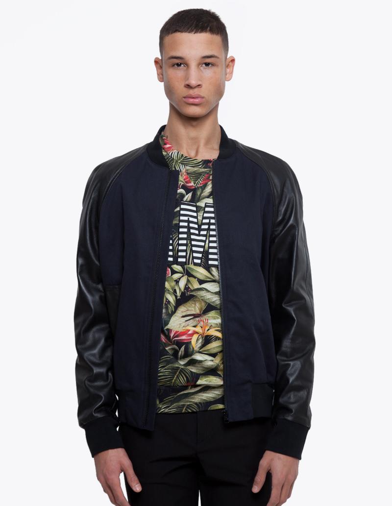 Юноша в синей куртке бомбер с кожаными рукавами, Ami