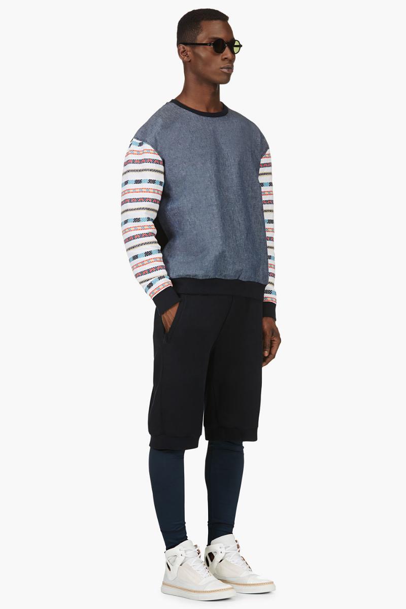 Мужчина в синих свободных шортах поверх леггинсов, в свитере из шамбре, и высоких кроссовках, всё Giuliano Fujiwara