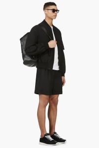 Мужчина в чёрном бомбере Y-3, широких свободных шортах и чёрных кроссовках на белой подошве Kris van Assche, с кожаным рюкзаком 3.1 Phillip Lim, солнечных очках Thom Browne