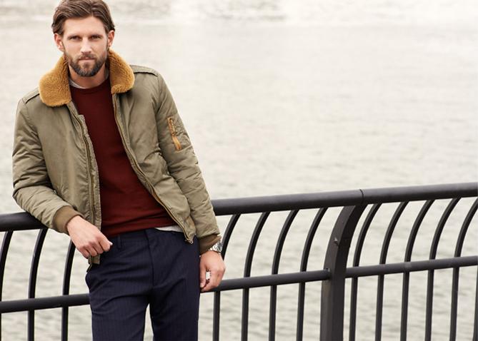 Мужчина в лётной куртке-бомбер цвета хаки с воротником из овчины